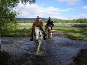 River crossing picture of Wyoming horseback riding vacation lovers